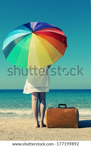 Summer vacation concept: beautiful model holding umbrella and posing at the seaside