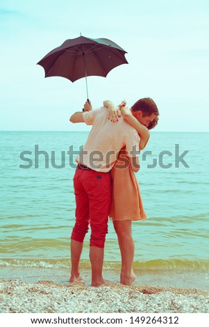 Summer vacation concept. Couple standing on beach near water, holding black umbrella and hugging each other. Hipster style. Happy together. Outdoor shot