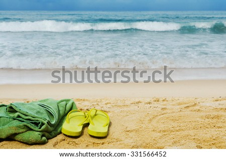 Summer vacation concept--Flipflops and towel on a sandy ocean beach - stock photo