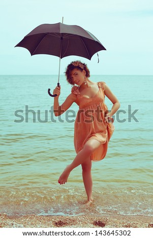 Summer vacation concept: portrait of a beautiful model with great tan wearing trendy dress, posing and standing at the seaside. Girl holding umbrella. Hipster style. Outdoor shot