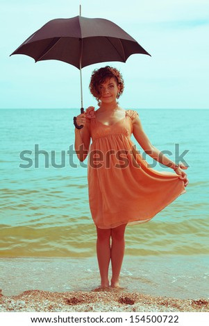Summer vacation concept: portrait of a beautiful model with great tan wearing trendy dress, posing and standing at the seaside. Girl holding umbrella. Hipster style. Outdoor shot - stock photo
