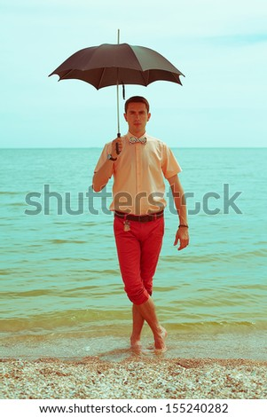 Summer vacation concept: portrait of a handsome model with great tan wearing trendy clothes, posing and standing at the seaside. Guy holding umbrella. Hipster style. Outdoor shot
