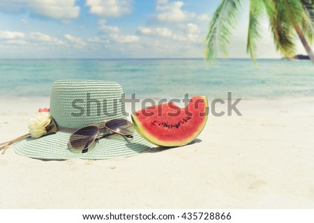 Summer vacation concept straw hat with sunglasses and melon fruit on sandy tropical beach - stock photo