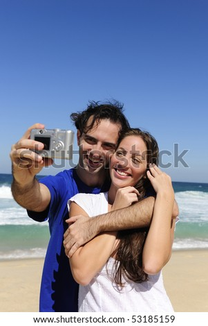 summer vacation: couple taking a photo with a digital compact camera - stock photo