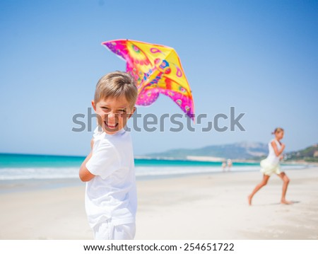 Summer vacation - Cute boy and girl flying kite beach outdoor. - stock photo