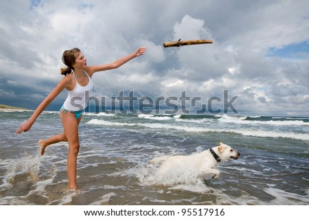 Summer vacation - girl with dog playing on the beach - stock photo