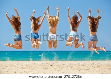 summer, vacation, holiday, happy people concept - a group of friends jumping and running on the beach - stock photo