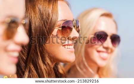 summer vacation, holidays, friendship and people concept - close up of smiling young women in sunglasses - stock photo