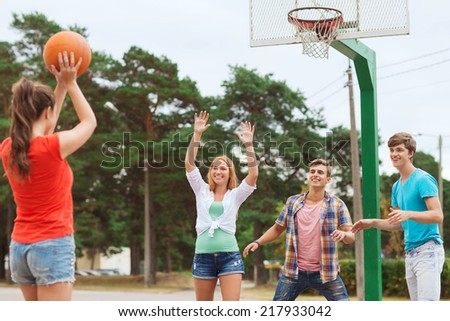 summer vacation, holidays, games and friendship concept - group of smiling teenagers playing basketball outdoors - stock photo