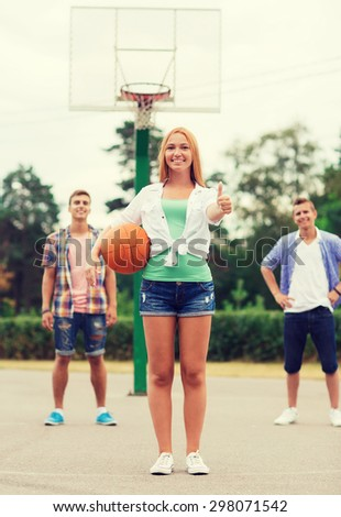 summer vacation, holidays, games, gesture and people concept - group of smiling teenagers playing basketball and showing thumbs up outdoors - stock photo
