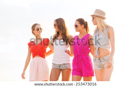 summer vacation, holidays, travel and people concept - group of smiling young women in sunglasses and casual clothes on beach - stock photo