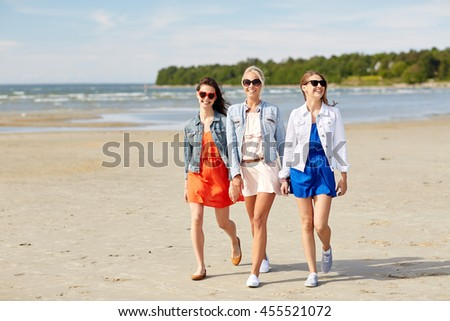 summer vacation, holidays, travel and people concept - group of smiling young women in sunglasses and casual clothes walking along beach