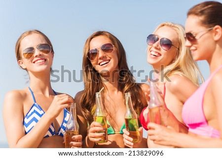 summer vacation, holidays, travel and people concept - group of smiling young women sunbathing and drinking on beach - stock photo