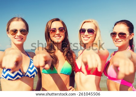 summer vacation, holidays, travel, gesture and people concept - group of smiling young women pointing finger on you on beach - stock photo