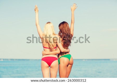 summer vacation, holidays, travel, gesture and people concept - two young women waving hands on beach from back - stock photo