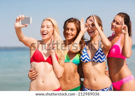 summer vacation, holidays, travel, technology and people concept- group of smiling young women on beach making selfie with smartphone over blue sky background - stock photo