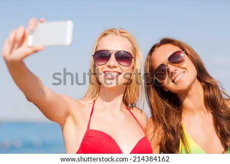 summer vacation, holidays, travel, technology and people concept - two smiling young women on beach making selfie with smartphone over blue sky background