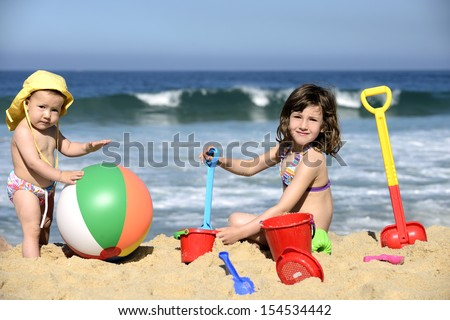 Summer vacation: Kids playing with beach toys in the sand - stock photo