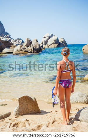 Summer vacation, lovely girl on the beach standing and looking at the sea