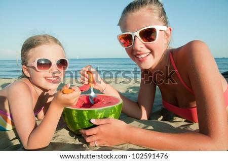 Summer vacation - lovely girls eating fresh watermelon on sandy beach - stock photo