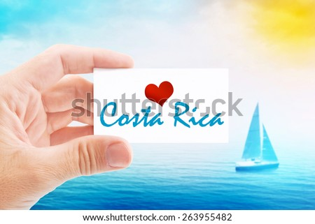 Summer Vacation on Costa Rica Beach, Person Holding Visiting Card for Summertime Holiday Message Love Costa Rica and Sailboat at Sea in Background. - stock photo