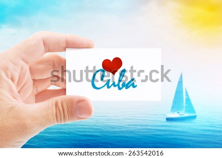 Summer Vacation on Cuba Beach, Person Holding Visiting Card for Summertime Holiday Message Love Cuba and Sailboat at Sea in Background. - stock photo