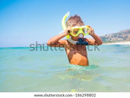 Summer vacation - Portrait of happy boy in face masks and snorkels, sea in background.