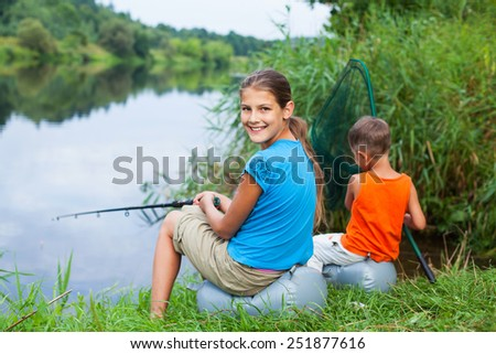 Summer vacation - Sister and brother fishing at the river - stock photo
