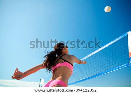 summer vacation, sport and people concept - young woman with ball playing volleyball on beach - stock photo
