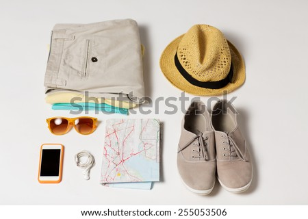 summer vacation, tourism and objects concept - close up of clothes, smartphone, personal stuff and travel map - stock photo
