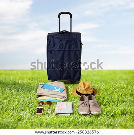 summer vacation, tourism and objects concept - travel bag, map, air ticket and clothes with personal stuff over blue sky and grass background - stock photo