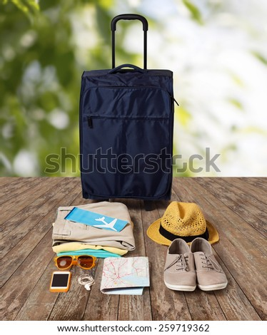 summer vacation, tourism and objects concept - travel bag, map, air ticket and clothes with personal stuff over wooden floor and nature background - stock photo