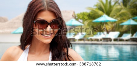 summer vacation, tourism, travel, holidays and people concept -face of smiling young woman with sunglasses over beach and swimming pool background - stock photo