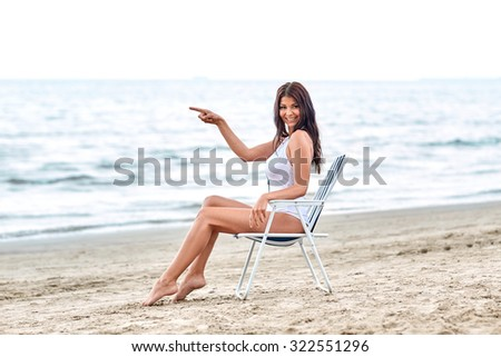 summer vacation, tourism, travel, holidays and people concept - smiling young woman sunbathing in lounge or folding chair on beach - stock photo