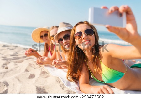 summer vacation, travel, technology and people concept - group of smiling women in sunglasses and hats making selfie with smartphone on beach