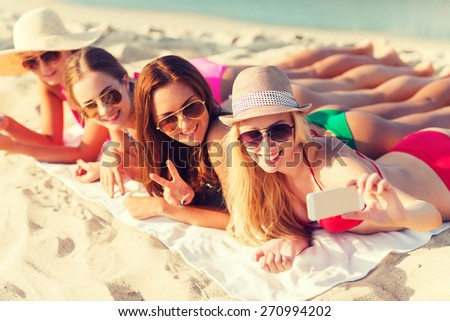 summer vacation, travel, technology and people concept - group of smiling women in sunglasses and hats making selfie with smartphone on beach - stock photo
