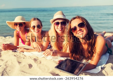 summer vacation, travel, technology and people concept - group of smiling women in sunglasses with tablet pc computers lying on beach - stock photo