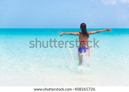 Summer vacation woman happy running into ocean on beach splashing water cheering full of joy and excitement on holidays travel. Exhilarated girl tourist in bikini with arms outstretched cheerful. - stock photo