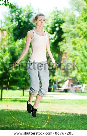 Summer vacation - woman with skipping rope at park - stock photo