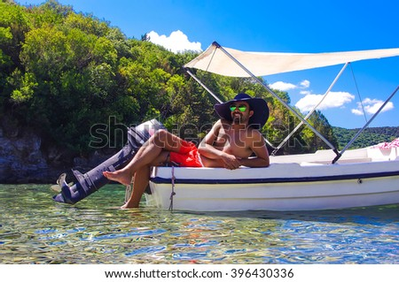Summer vacation. Young man resting in a boat  wearing big women's hat. Fun. Greece. Syvota. Boat trip