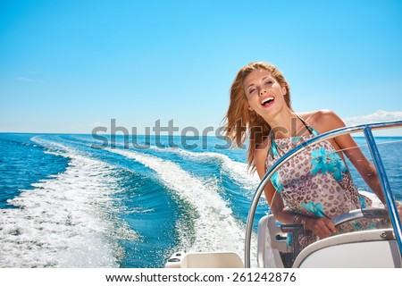 Summer vacation - young woman driving a motor boat  - stock photo