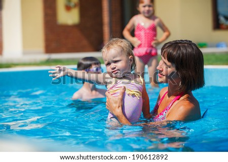 Summer vacations concept. Happy mother and daughter playing in blue water of swimming pool. - stock photo