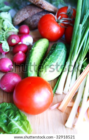 Summer vegetables - tomatoes, cucumbers, radish, spring onion, chard, and rye bread on a wooden kitchen board, ready for sandwich making, blur background, vertical - stock photo