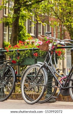 Summer view of bicycles with flowers on a canal bridge in the Dutch city Amsterdam - stock photo