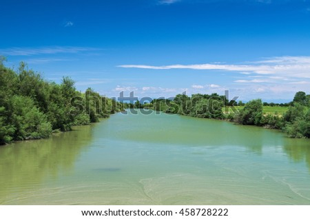Summer view of river Lemene in the Venetian Plain with the Alps mountains in the background