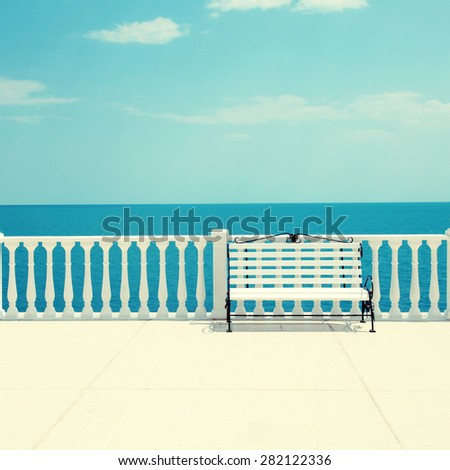 Summer view with classic white balustrade, bench and empty terrace overlooking the sea (Italy). Square toned image, instagram effect - stock photo