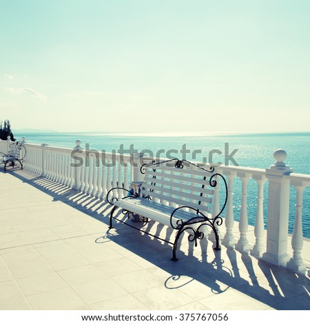 Summer view with classic white balustrade, benches and empty terrace overlooking the sea, sunlight. Square toned image, instagram effect - stock photo