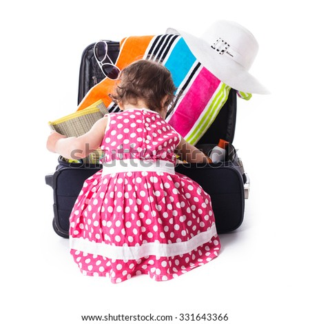 Summer voyage with children - toddler girl helps to put accessories for vocations into the bag - stock photo
