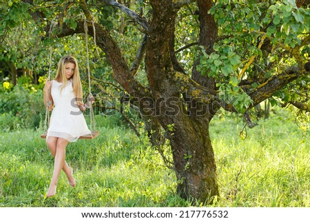 Summer, warm. Cute, young girl on a swing - stock photo