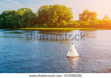 Summer water sunset landscape - trees along the bank of the river and buoy on the water under warm sunset light. Summer landscape natural view. - stock photo